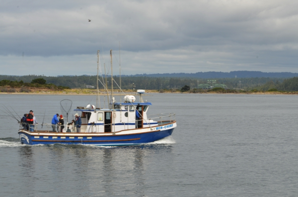 Fishing charter boat with the mile-long Coos Bay bridge in the background as seen from Bandon Harbor