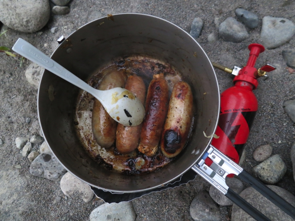 A dinner of chicken brats, sauerkraut and fried sweet onions