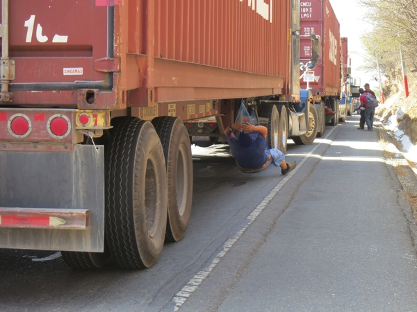 A driver takes advantage of the traffic, napping under his truck.  We enjoyed the shade provided by the stopped vehicles