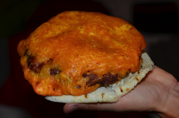 Battered, deep fried meat patty on an arepa