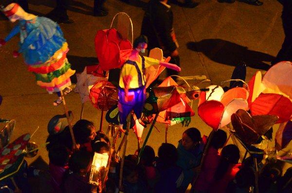 parade of kids carrying candle-lit lanterns