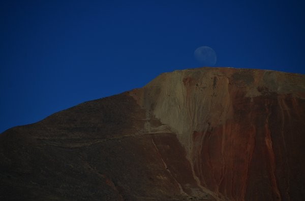 The moon setting over the mountains