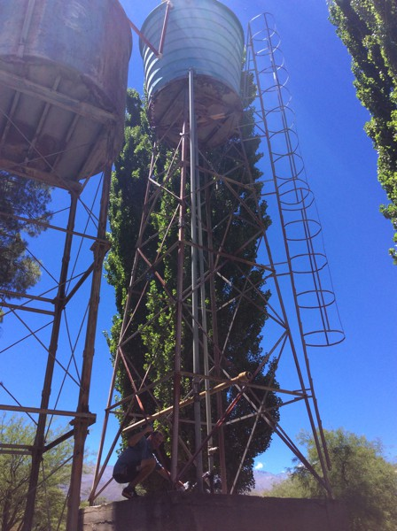 Scott collecting water from runoff of a water tower.